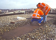 first gravel is removed with broom to expose bitumen for reliable and stable frame placement