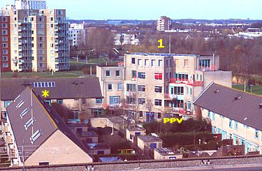 Local view of rental appartment complex with 22 solar panels on top of tower (1) and 6 on slanted roof (*); Polder PV lives on ground level (PPV).