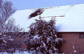 Snow cover on small PV-system on neighbour's slanted roof.